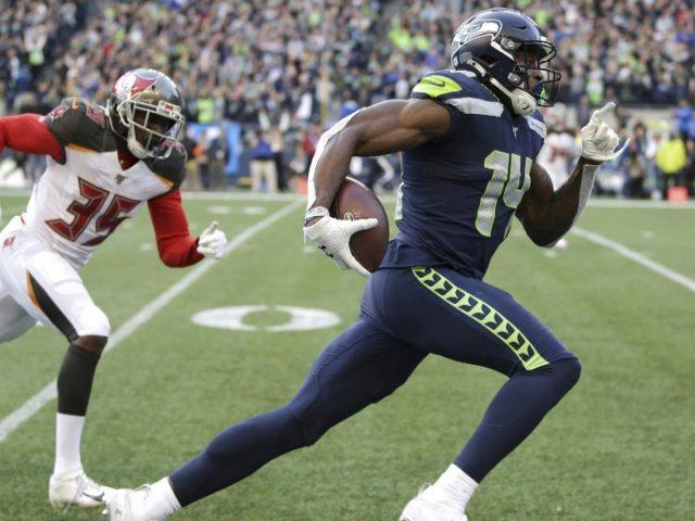 Меткалф бежит держа мяч в одной руке одетый в синюю спортивную одежду и шлем ДК Меткалф