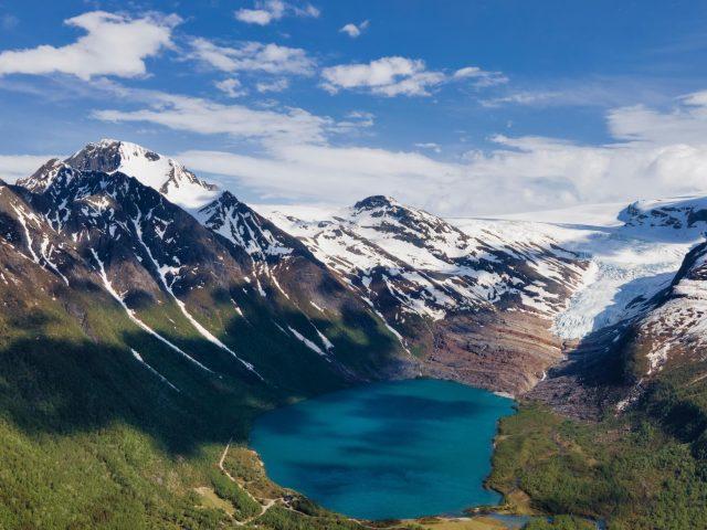 Озеро окруженное белыми покрытыми горами под облачным голубым небом в свартисватнете Норвегия природа