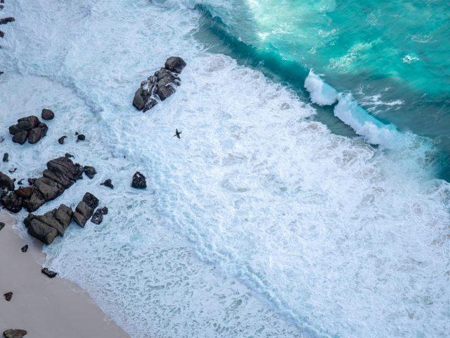 Коричневые скалы на белом песчаном пляже