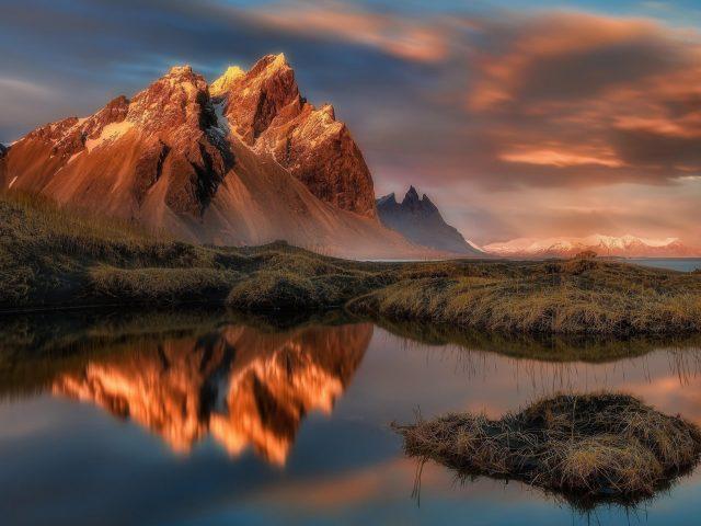 Отражение гор на воде озера с облаками и голубым небом природа