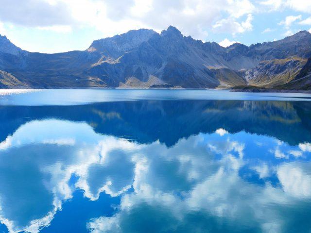 Бело — зеленые покрытые горы под облачным голубым небом рядом с озером с отражением природы