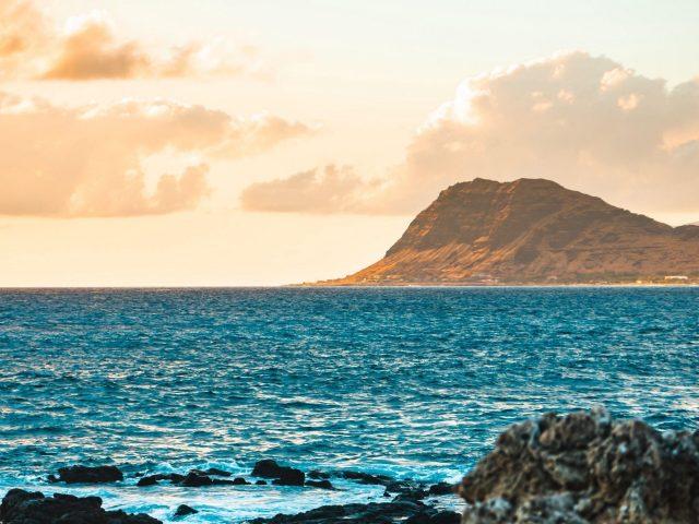 Коричневая гора перед голубым океаном в дневное время природа