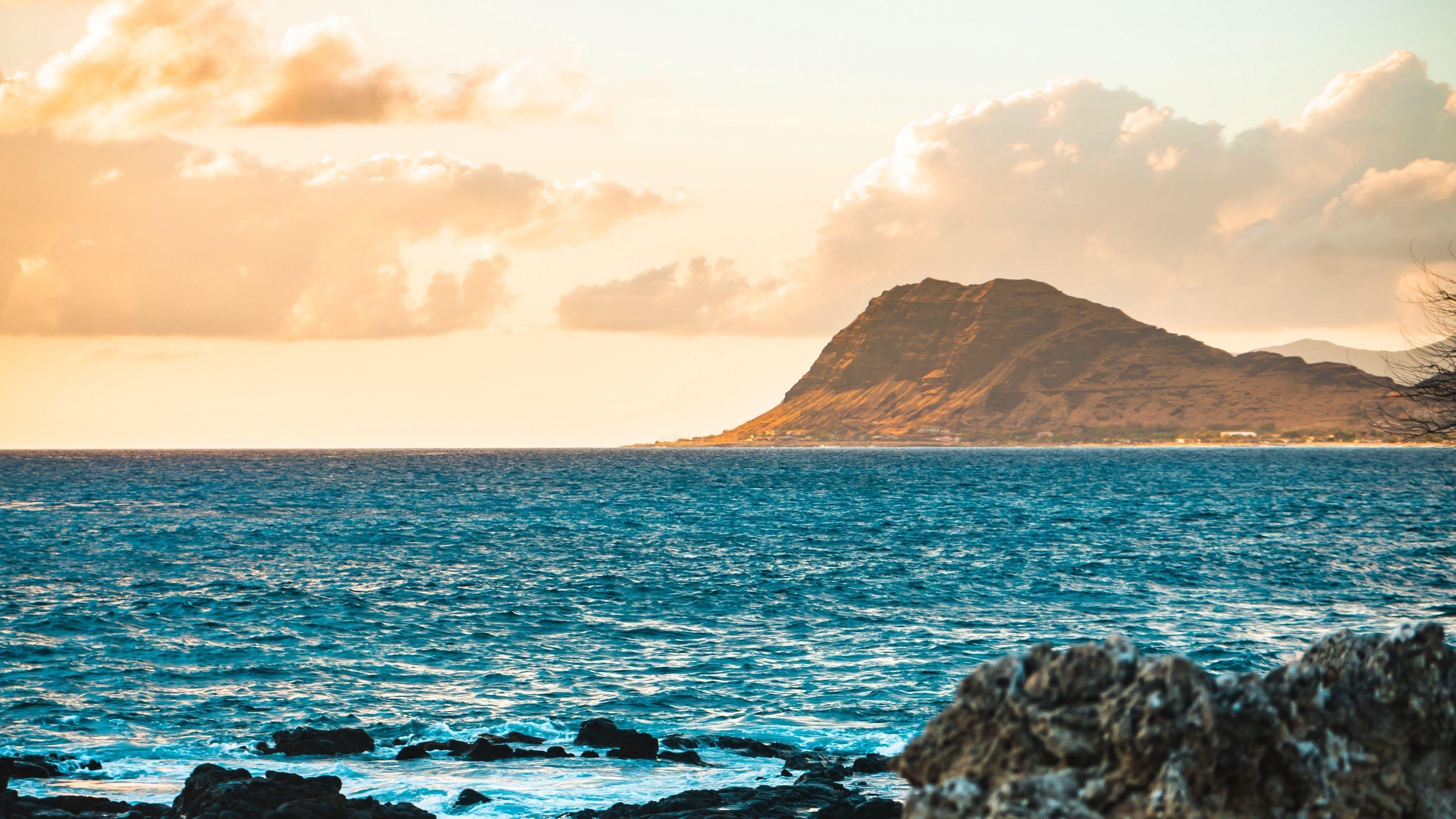 Коричневая гора перед голубым океаном в дневное время природа обои скачать