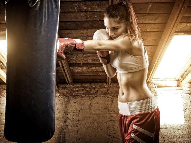 Брюнетка с конским хвостом пробивает боксерский мешок одетая в белое красное платье бокс