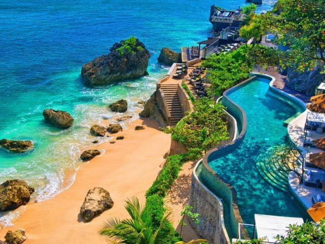 Курорт с бассейном и хижиной рядом с пляжем природа
