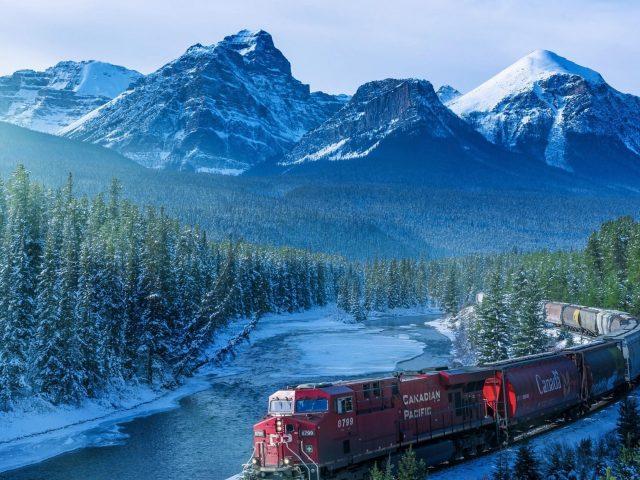 Пейзажный вид на белые покрытые горы и красный поезд на рельсах природа