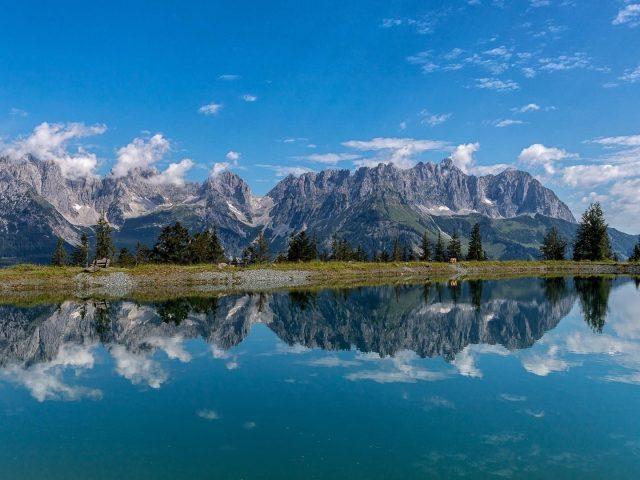 Пейзаж покрытой зеленью горы под голубым небом с отражением на озере природы