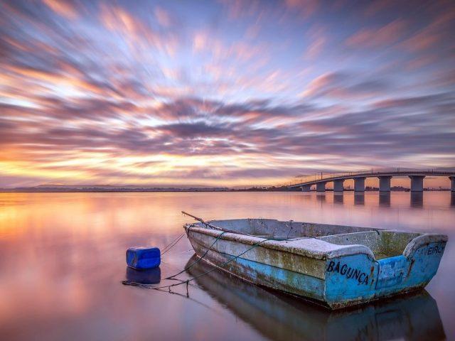 Транспортные средства лодка стоит одна под закатом солнца