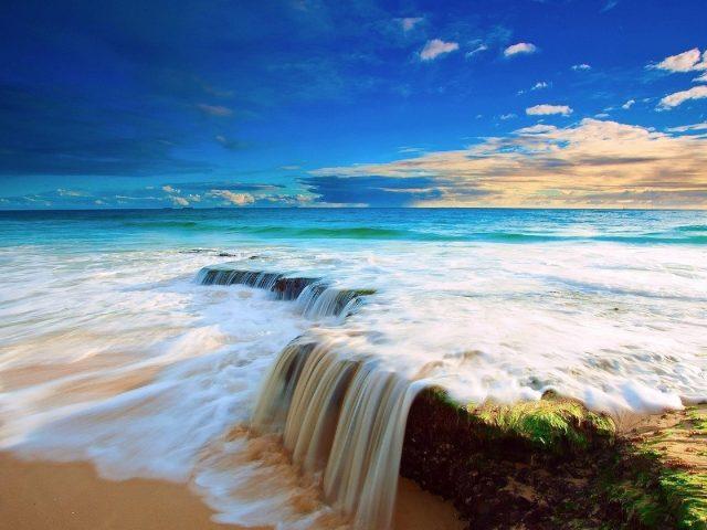 Волны переполняют переднюю часть океана под голубым небом природа