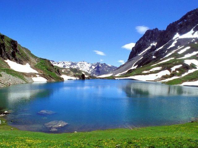 Озеро между белыми черно зелеными покрытыми горами днем под голубым небом природа