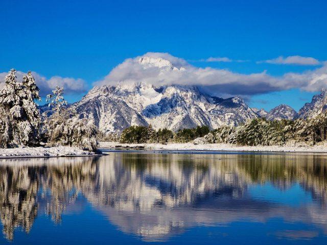 Облако на белой покрытой горе в национальном парке Гранд Титон с отражением на реке в вайомингской природе