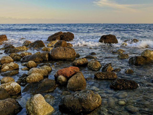 Белые и коричневые морские камни волны под голубым небом природа