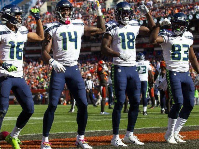Меткалф с игроками одетыми в бело голубую спортивную одежду и шлем на фоне игроков и зрителей ДК Меткалф