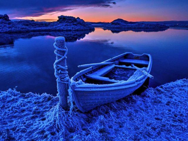 Замерзшая лодка на водоеме во время заката природа