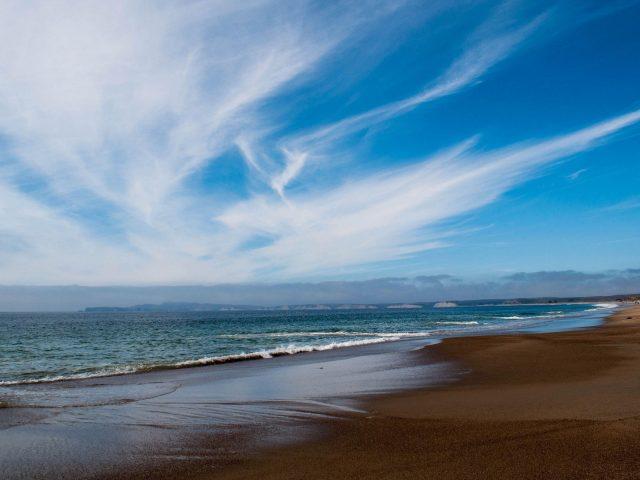 Океанские волны пляжный песок под белыми облаками голубое небо природа