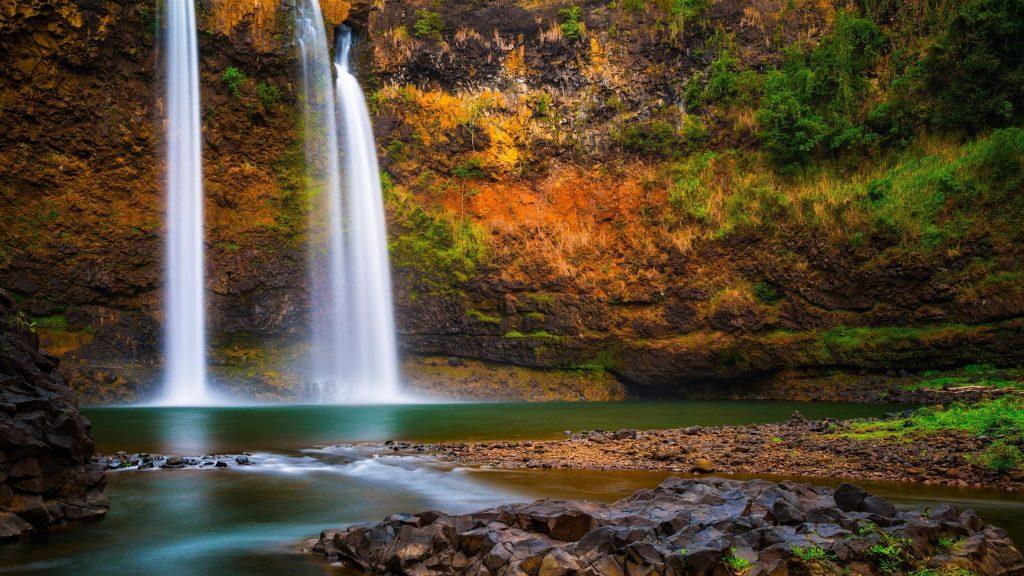 Красивый водопад, льющийся на реку на фоне скалы природа обои скачать