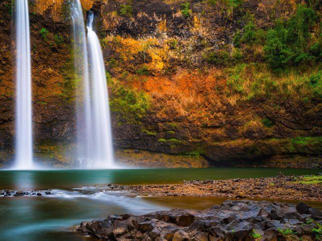 Красивый водопад, льющийся на реку на фоне скалы природа