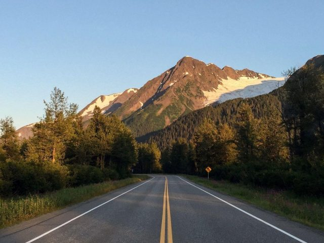 Дорога между деревьями пейзаж вид на скалистые горы под голубым небом природа