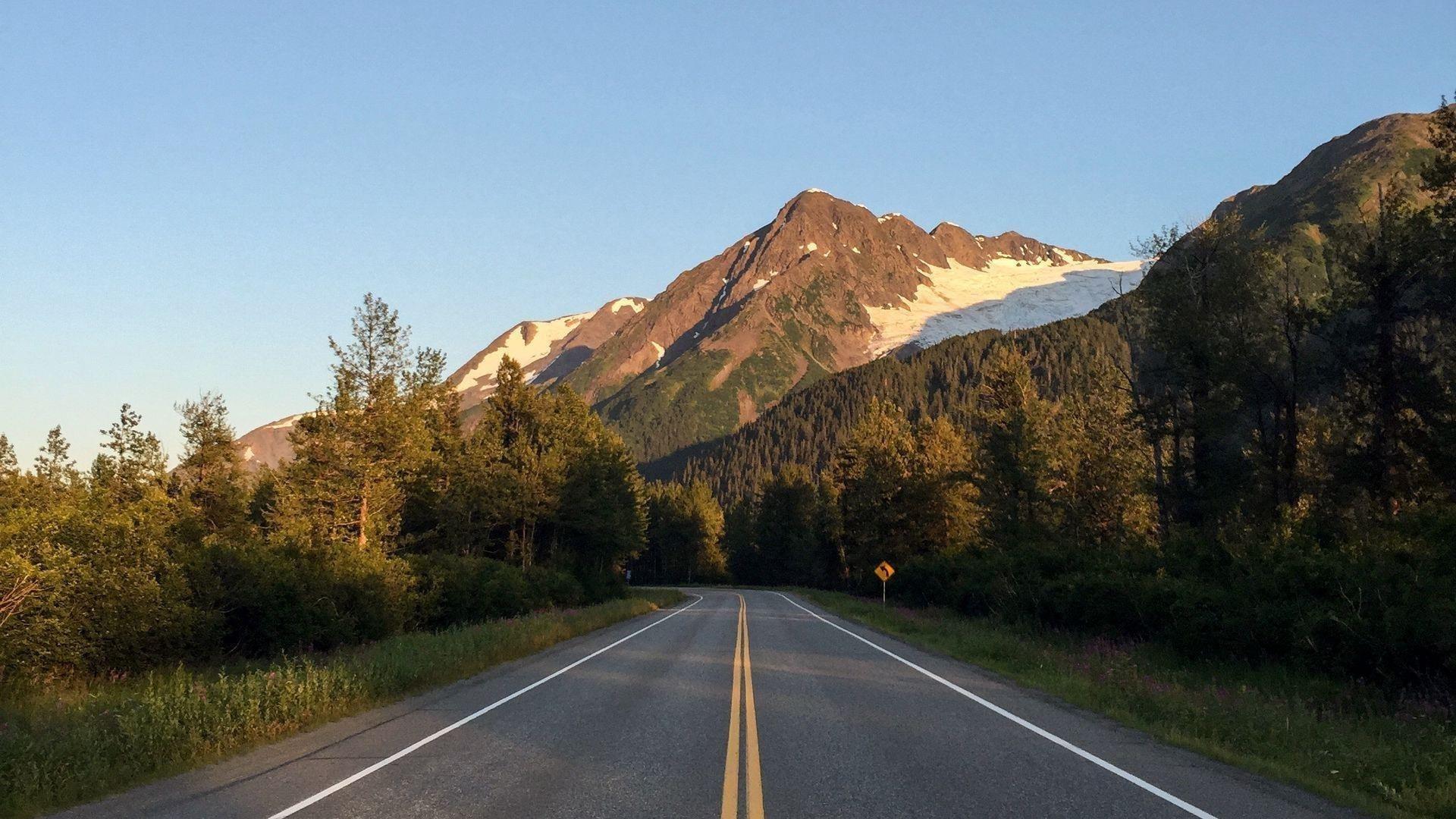 Дорога между деревьями пейзаж вид на скалистые горы под голубым небом природа обои скачать