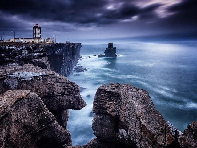Рукотворный маяк между берегом моря с черно-белыми скалами природа