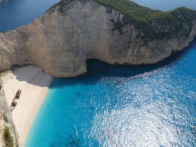 Аэрофотоснимок покрытой деревьями скалы между океанской природой
