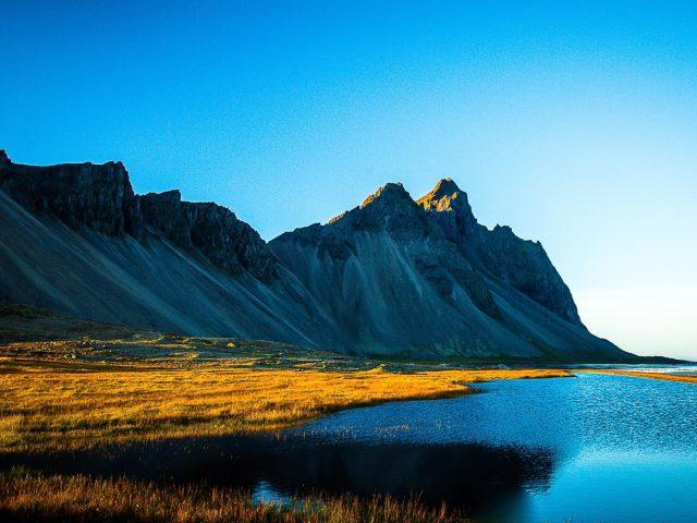 Покрытое травой озеро рядом с белой покрытой горой под голубым небом в дневное время природа
