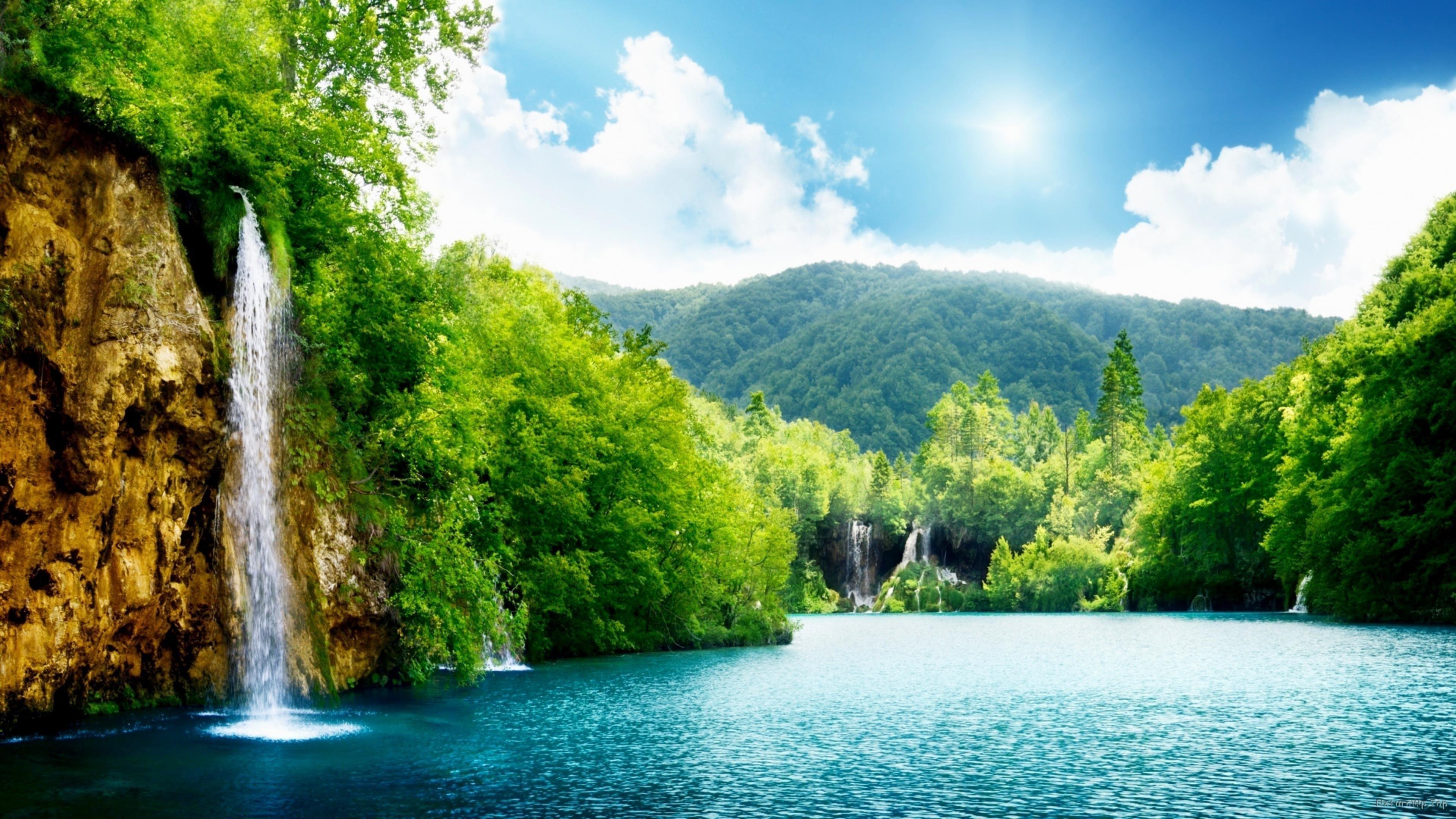 Водопады рядом с зелеными листьями деревьев под голубым небом природа обои скачать
