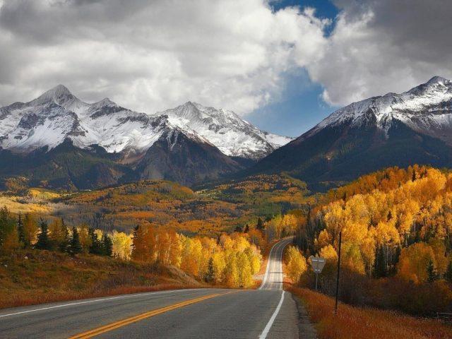 Вверх и вниз по дороге между желто-зелеными деревьями, покрытыми лесом, на фоне белых покрытых гор, под белыми облаками, голубым небом, природой