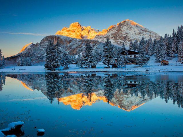 Заснеженные сосны и покрытые желтым снегом горы отражение природы озера