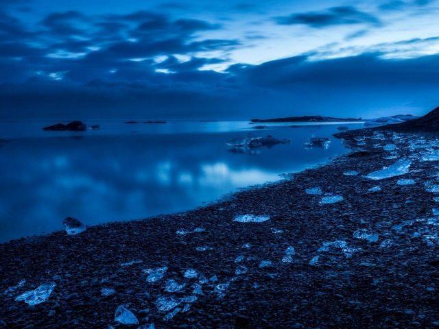 Пасмурное голубое небо над спокойным водоемом с отражением природы