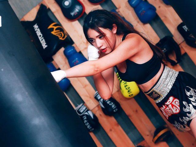 Черноволосая девушка с помадой одета в черное платье пробивает боксерский мешок бокс