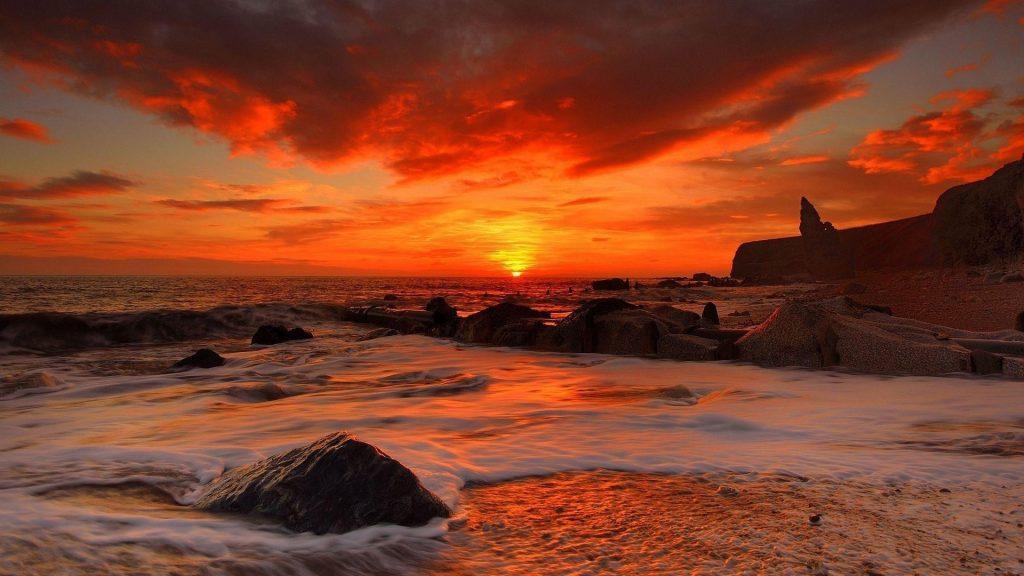 Морские волны на скалах во время восхода солнца под красным облачным небом природа обои скачать
