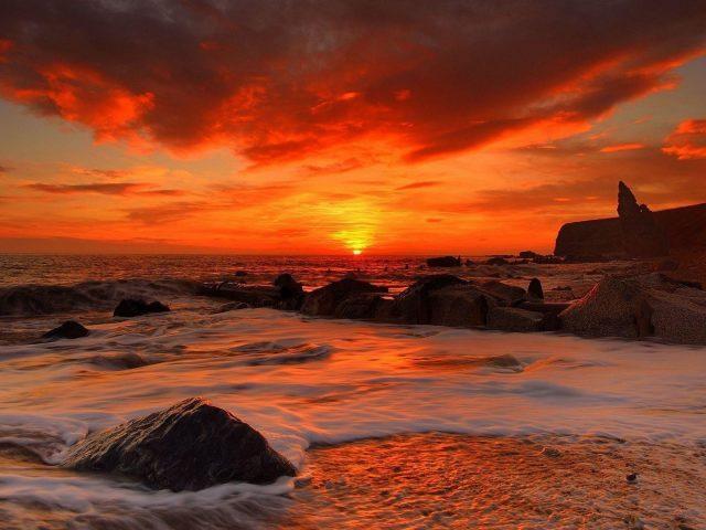 Морские волны на скалах во время восхода солнца под красным облачным небом природа