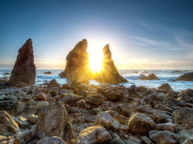 Солнечный свет, проходящий сквозь скалы между берегами моря под голубым небом в дневное время природа