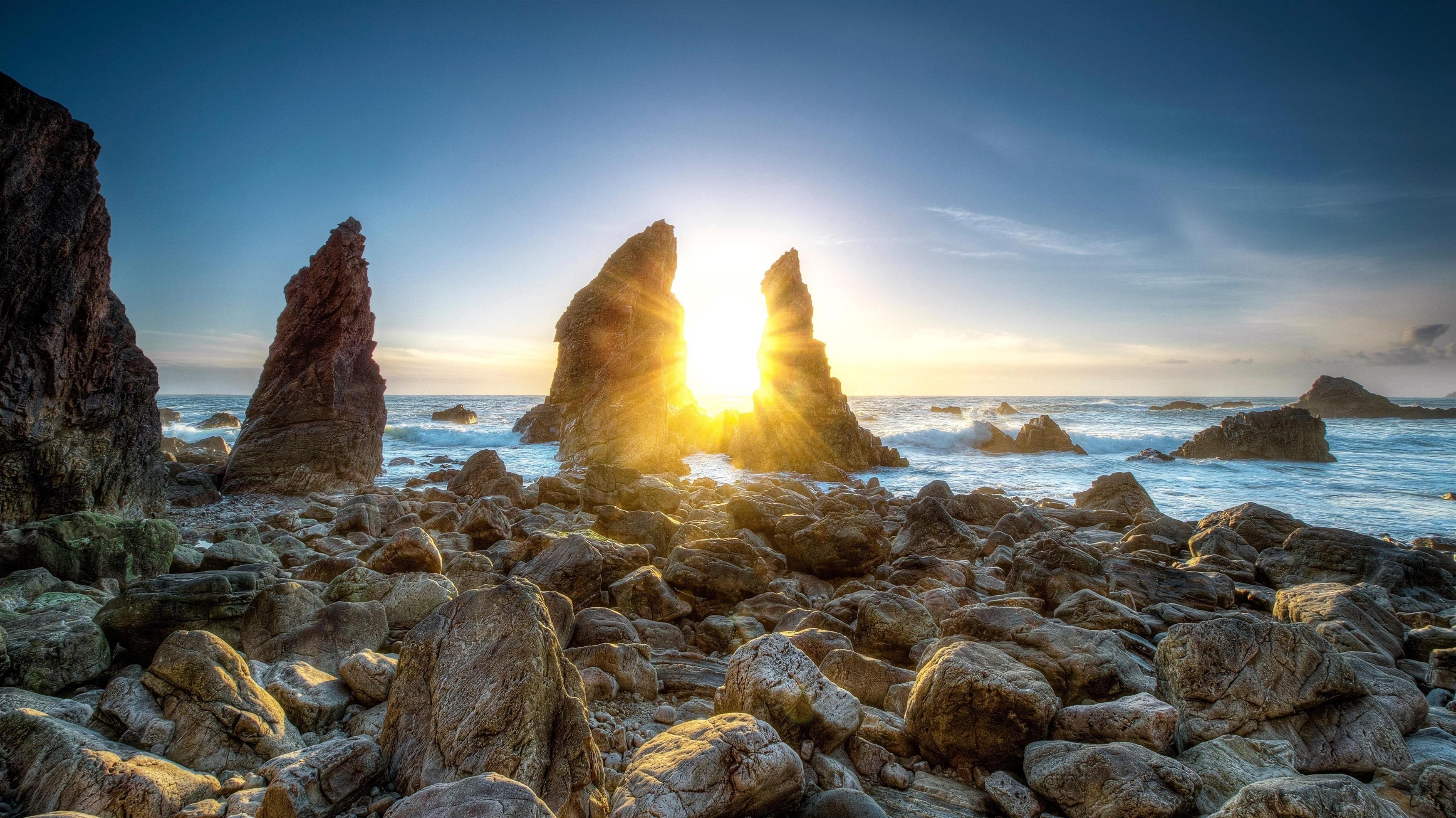 Солнечный свет, проходящий сквозь скалы между берегами моря под голубым небом в дневное время природа обои скачать