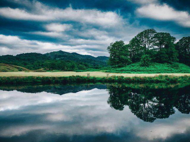 Пейзаж вид на зеленые деревья покрытые горы под облачным голубым небом природа