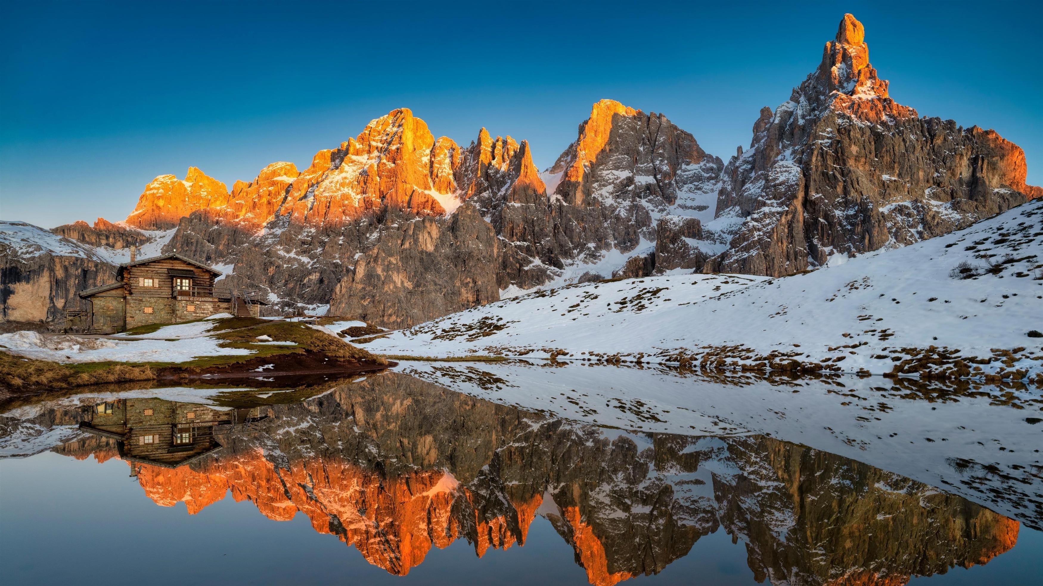 Заснеженная гора с отражением на воде солнечных лучей природа обои скачать