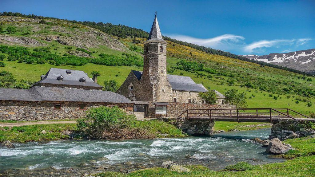 Пейзажный вид на горный склон и церковь с мостом над водой природа обои скачать