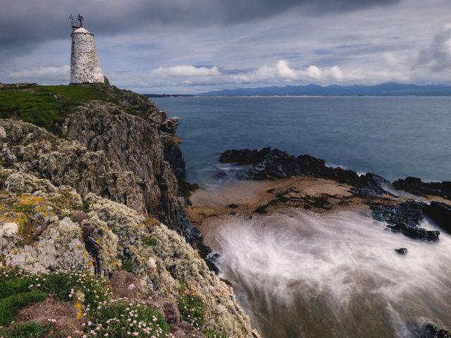 Зеленая покрытая Гора между маяком перед морским берегом в дневное время природа