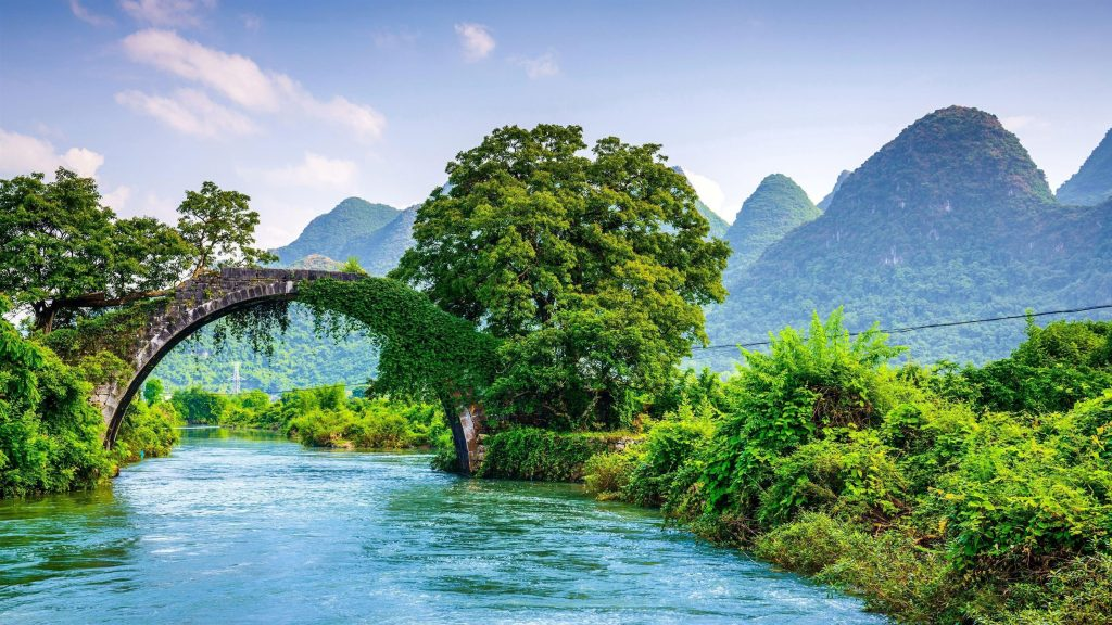 Арка над рекой между зелеными деревьями с пейзажным видом на горы природу обои скачать