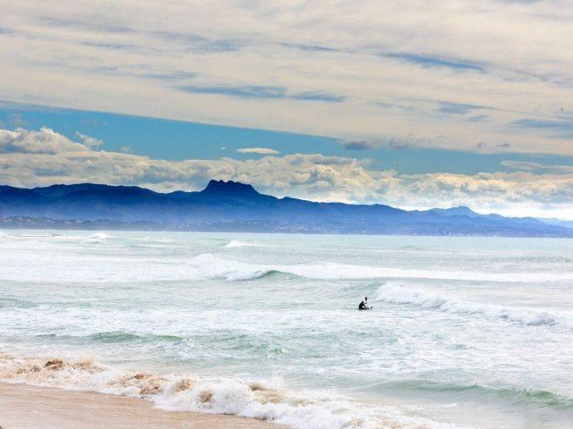 Океанские волны побережье человек гребет пейзаж вид на горную природу