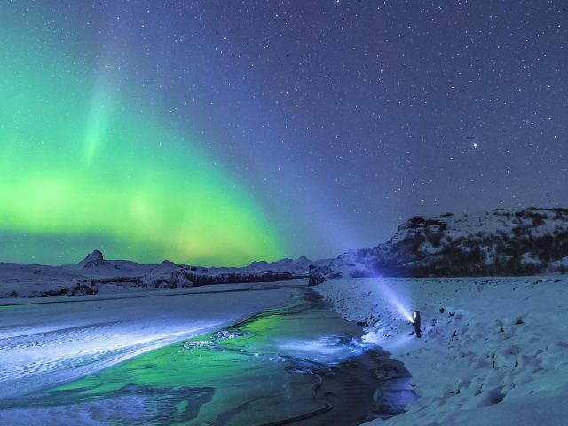 Человек, стоящий под полярным сиянием природы
