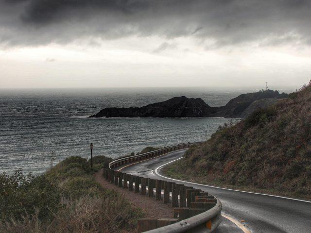 Поворот дороги забор склон зеленая трава океан скалистые горы черные белые облака небо природа