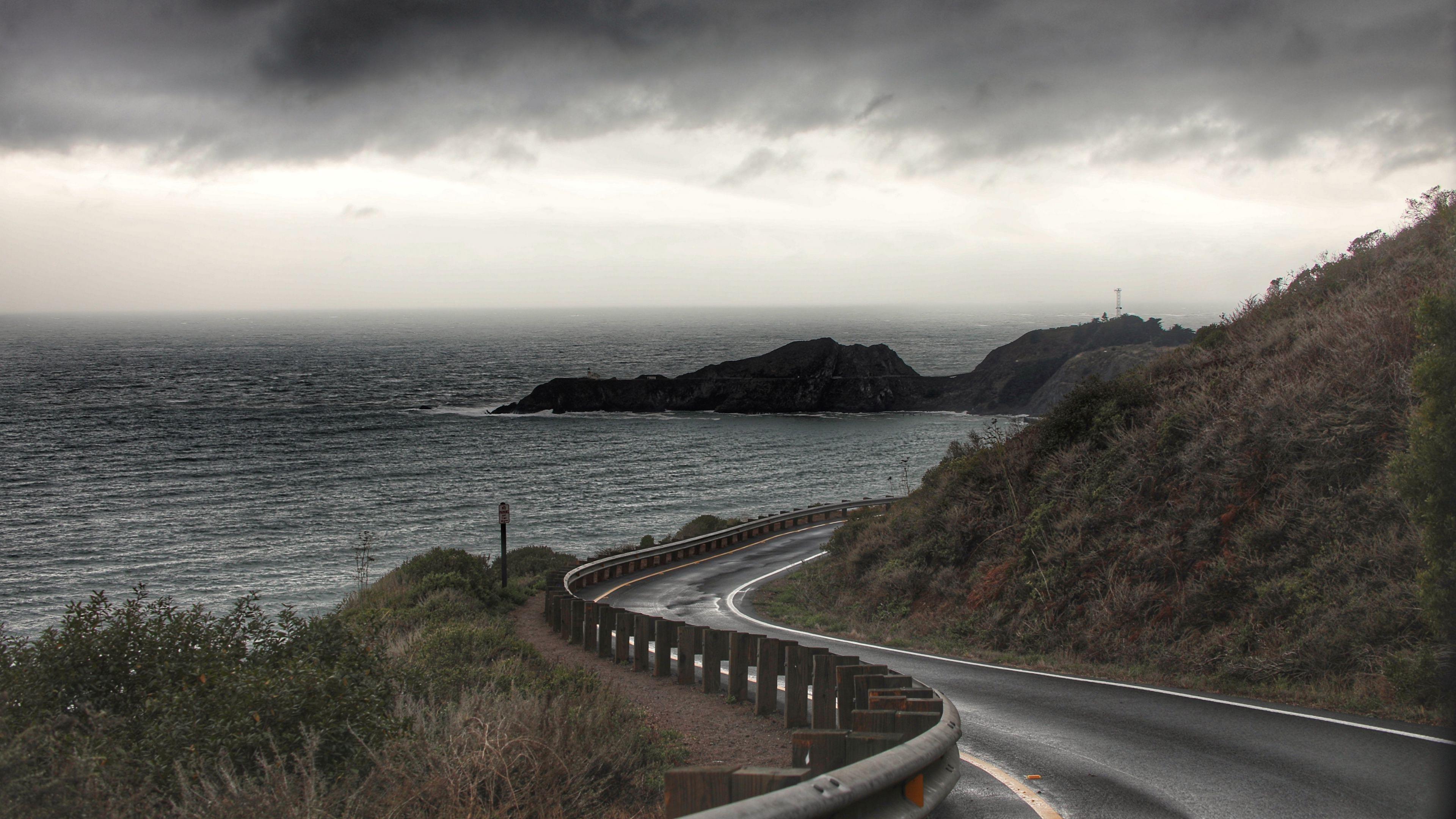 Поворот дороги забор склон зеленая трава океан скалистые горы черные белые облака небо природа обои скачать
