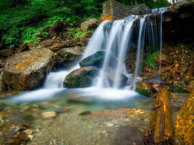 Водопад между деревьями, скалами в дневное время