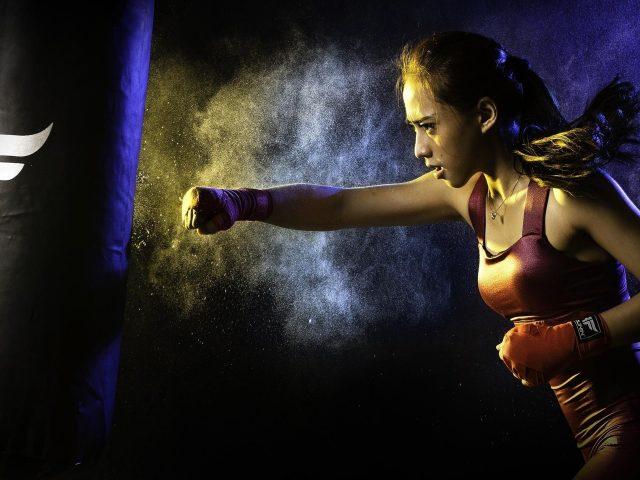 Девушка пинает боксерский мешок бокс