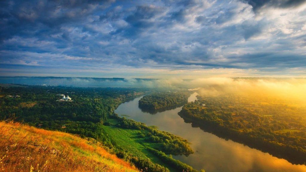 Вид с высоты птичьего полета на покрытые туманом горы под облачным небом и реку между зелеными деревьями, покрытыми лесной природой обои скачать