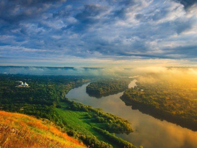 Вид с высоты птичьего полета на покрытые туманом горы под облачным небом и реку между зелеными деревьями, покрытыми лесной природой
