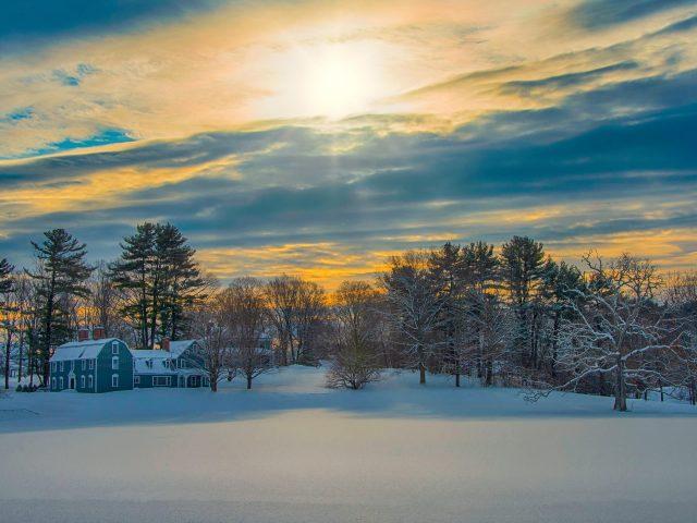 Заснеженный дом под небом во время заката зимы
