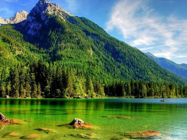 Прекрасный пейзаж с видом на зеленые деревья, покрытые горами под бело-голубыми облаками, камни на океанской природе